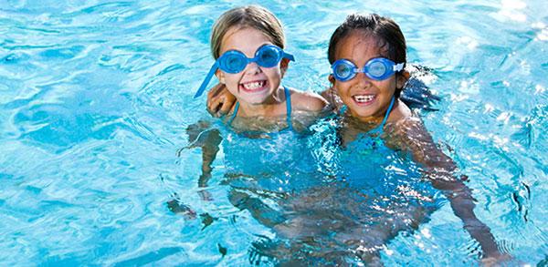 Niñas en piscina bañándose con gafas protectoras, previsión de Socorrismo y salvamento acuático